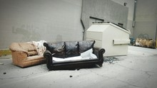 Old Sofas By Garbage Bin Outside Building