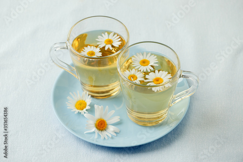 Photo Herbal tea with fresh chamomile flowers in glass teacup on blue plate, seasonal