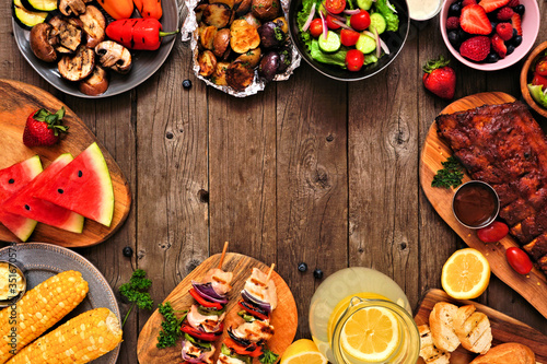 Fototapeta Summer BBQ or picnic food frame over a rustic wood background. Assortment of grilled meats, vegetables, fruits, salad and potatoes. Top down view with copy space. obraz