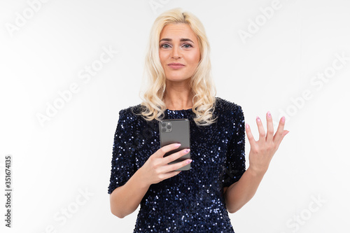 Photo pensive lady in a shiny dress surfing the Internet from the phone on a white bac