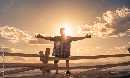 Fényképezés Happy young man sitting on a hill at sunset with arms up enjoying the sunshine and feeling free