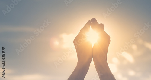 Fototapeta Woman's hands holding the sun at dawn. Freedom and spirituality concept.  obraz