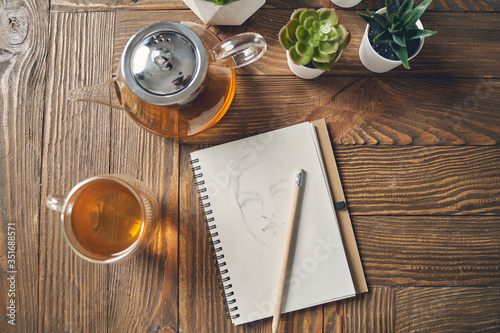 Fototapeta Notebook with female face sketch and tea on wooden table obraz