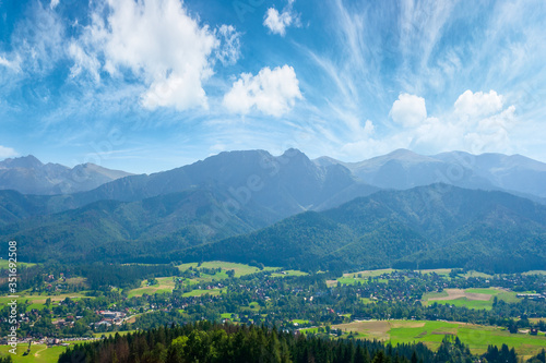 Fototapeta high tatra mountain ridge. poland travel destination. beautiful summer landscape in evening light. sunny weather with fluffy clouds on the blue sky. obraz
