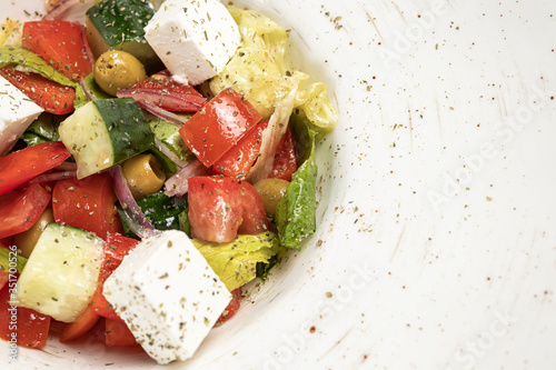 Greek salad with olives and cheese on a round white plate Canvas Print