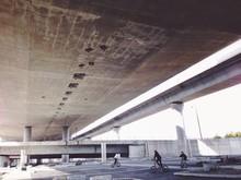 Boys Cycling Under Bridge