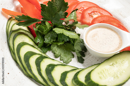 Fototapeta vegetables sliced cucumbers, tomatoes with sauce on a white plat obraz