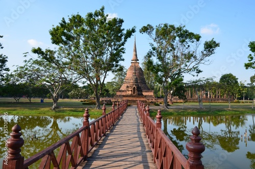 Fototapeta A red bridge is leading to Wat Sra Sri, a beautiful temple in the historical par