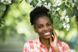 beautiful young african woman near a flowering tree