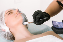 Cosmetologist's Hand In A Protective Rubber Glove Uses A Special Brush To Apply A Silver Ointment To A Female Patient's Neck Lying On A Pillow