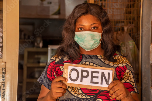 local african business owner holding a open sign in her store Wallpaper Mural