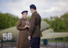 Young Adult Man And Woman In The Uniform Of Pilots Of The Soviet Army Of The Period Of World War II. Military Uniform With Shoulder Straps Of A Major And A Cap On His Head. Photo In Retro Style.