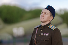A Young Adult Male Pilot In The Uniform Of Pilots Of The Soviet Army Of The World War II Period. Military Uniform With Shoulder Straps Of A Major And A Cap On His Head. Photo In Retro Style.