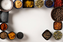 Group Of Bowls Full Of Spices All Around On A White Surface
