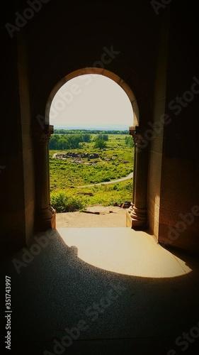 Fotografie, Obraz Grassy Field Seen Through Archway