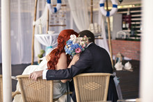 Nautical Style Wedding. Kiss Of The Newlyweds. The Bride And The Groom Are Hiding Behind A Bouquet.