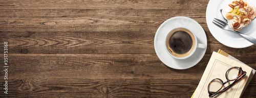 Photo コーヒーカップ、本、メガネ、ケーキの乗った皿のある木製のテーブル。