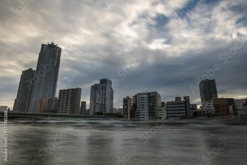 View Of Skyscrapers By River Against Cloudy Sky