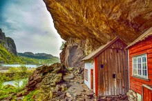 Houses Under Rock Formation Against Sky