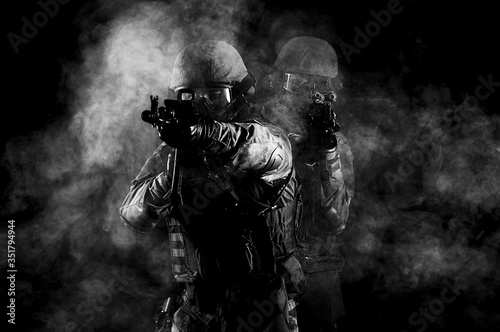 Fotografía American soldiers in combat ammunition with weapons in the hands of equipped laser sights are in battle order