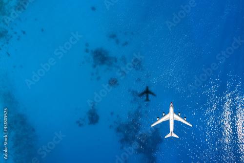 Obraz Reisekonzept mit einem Flugzeug über blauem Meer und Textfreiraum - fototapety do salonu