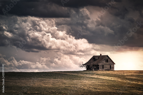 Fototapeta Old wooden farmhouse in the countryside at sunset with storm  clouds in the sky
