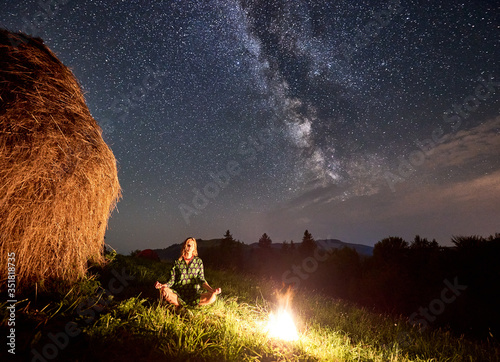 Valokuvatapetti Amazing starry night in the mountains, girl is sitting on the grass near a bonfi