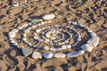 A Spiral Of Stones Is Laid Out On The Sand. Pictures Of Stones. Beach Ornament. Natural Background Of Stones. Entertainment On The Beach. Beach Holiday. Infinity.