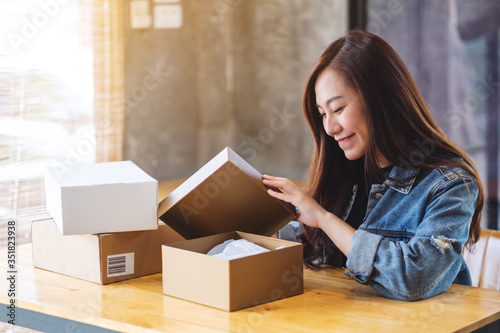 Fototapeta A beautiful young asian woman receiving and opening a postal parcel box at home for delivery and online shopping concept obraz