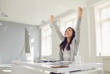Happy Successful Smiling Business Woman Raised Her Hands Up While Sitting At A Table In The Office.