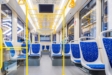 Interior design of a modern bus. Empty bus interior. Public transport in the city. Passenger transportation. Bus with blue seats and yellow handrails.