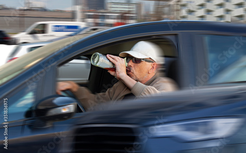 фотографія Careless male driver with sunglasses and cap drinking liquor from a bottle and driving in heavy traffic