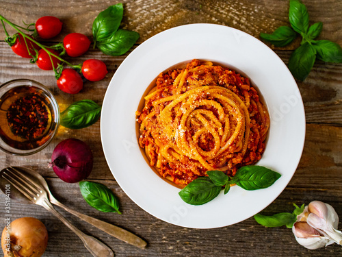 Fototapeta Spaghetti with tomato sauce, meat and parmesan on wooden background  obraz