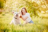 Fototapeta Zwierzęta - Best friends, young girl hugs labrador retriever dog and plays in park on summer day, sunlight