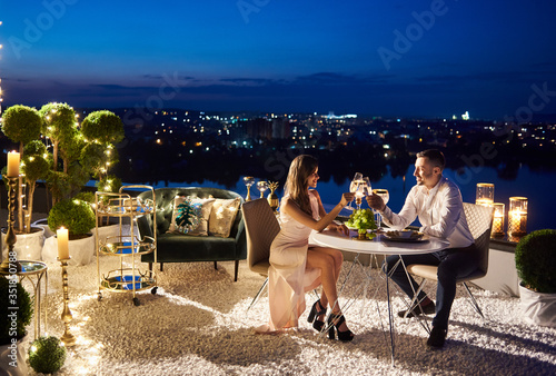 Obraz Beautiful couple sitting at the table and clinking glasses of champagne. Charming lady enjoying romantic date with boyfriend at rooftop restaurant with night cityscape on background. Concept of love. - fototapety do salonu
