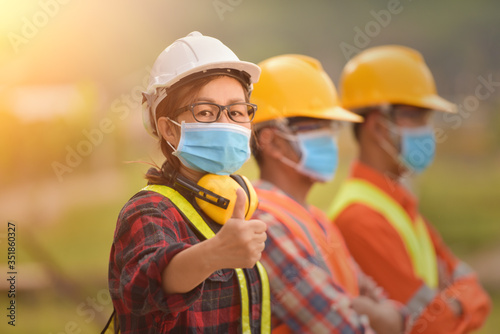 Obraz Corona or Covid-19 wear masks during the design of construction. New normal.Industrial engineering team wears a COVID 19 protective mask. Workers wear a quarantine face mask. - fototapety do salonu