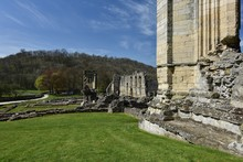 Abandoned Rievaulx Abbey By Grassy Field On Sunny Day