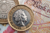 Business and finance, British economy and currency exchange concept with macro close up on one pound and two pounds coins and 10 GBP bank note