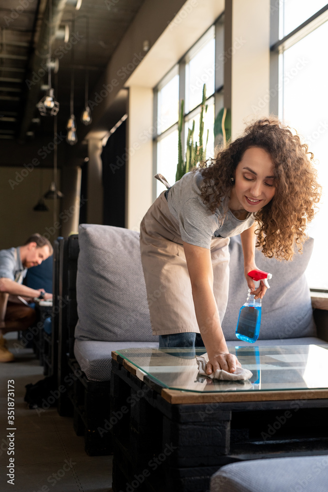 Fototapeta Young woman in workwear using detergent while bending over table