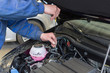 A professional mechanic is holding the oil dipstick of a car engine. Checking the engine oil level