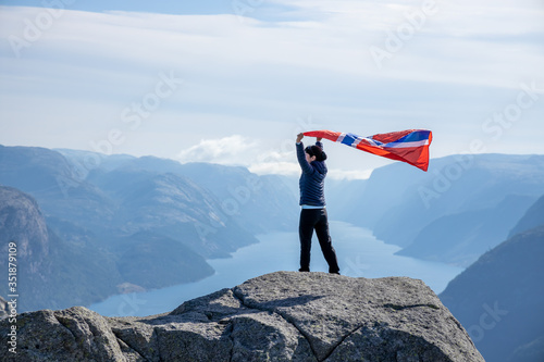 Obraz Woman with a waving flag of Norway on the background of nature - fototapety do salonu