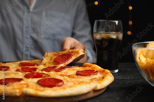 Woman taking tasty pepperoni pizza at table, closeup