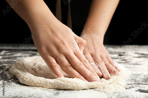 Woman kneading dough for pizza at grey table, closeup