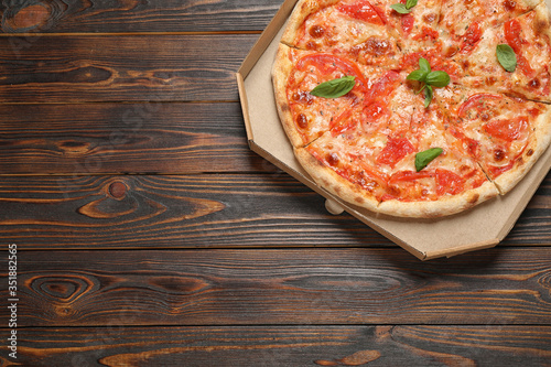 Delicious pizza Margherita on wooden table, top view. Space for text