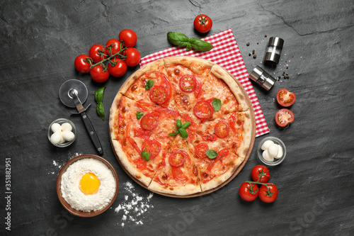 Delicious pizza Margherita and ingredients on dark grey table, flat lay