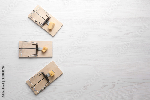 Cuadros en Lienzo Mousetraps with pieces of cheese and space for text on white wooden background, flat lay