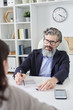 Serious grey-haired aged employer pointing at resume of female applicant