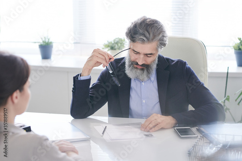 Aged pensive male hr manager holding eyeglasses by temple while reading resume