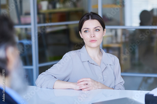 Pretty young brunette applicant in grey shirt looking at senior employer