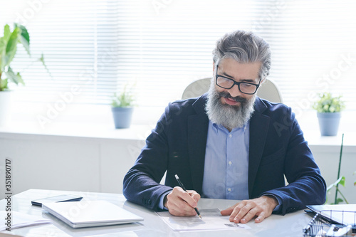 Experienced professional in eyeglasses and formalwear making notes on paper
